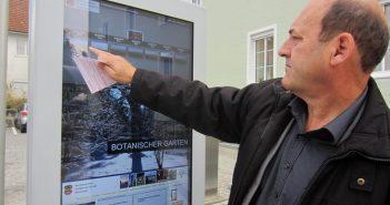 Bürgermeister Hans Baumann führt die vielen Funktionen des interaktiven Informationsbildschirms vor dem Gemeindeamt vor.